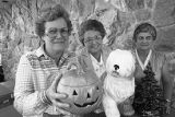 Three people posing with Jack-O-Lantern, fake white dog, and Christmas tree
